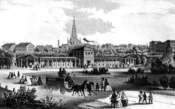 """Das Mineralbad Berg im Ursprungszustand von 1856. Rechts am Bildrand das 1872 eingerichtete """"Kurtheater Berg"""", im Hintergrund die neue Berger Kirche von 1855. (Lithografie, 1872)"""