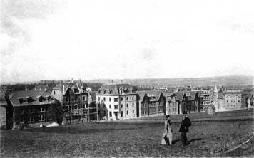 """Eduard Pfeiffer und seine Frau Julie vor der im Bau befindlichen """"Kolonie"""". (Fotografie, 1895)"""